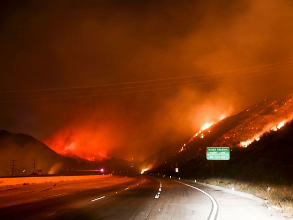 PHOTO: Flames burn next to the Interstate 15 as the Blue Cut wildfire rages near Cajon Pass, north of San Bernardino, California, Aug. 16, 2016.