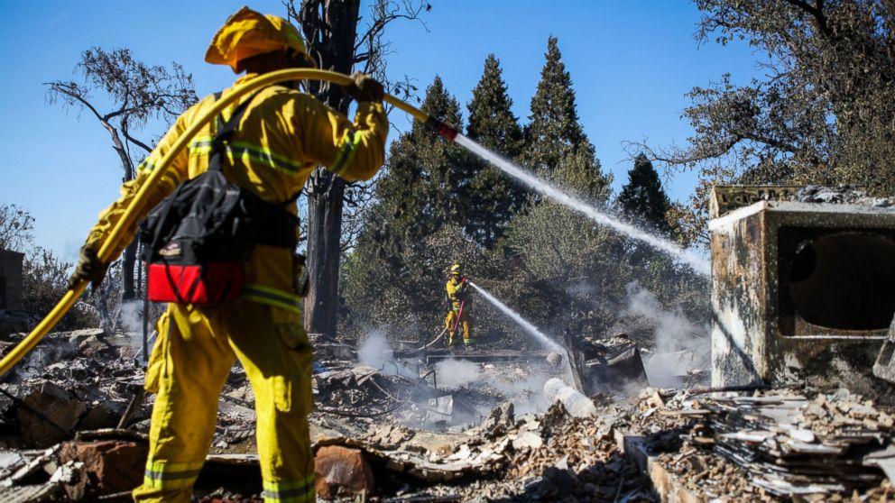 A firefighter works to contain embers on the remains of a house destroyed in the Clayton Fire are seen in Lower Lake, California, Aug. 15, 2016.