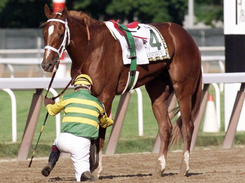 PHOTO: Jockey Chris Antley checks the leg of Charismatic after falling off the horse just past the finish line during the 131st running of the Belmont Stakes, June 5, 1999, Elmont, New York.