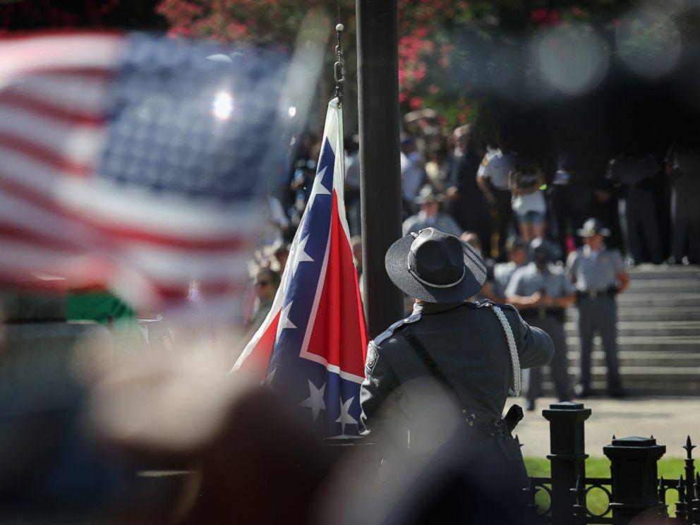 PHOTO: A South Carolina state police honor guard lowers the Confederate flag from the Statehouse grounds on July 10, 2015, in Columbia, S.C.