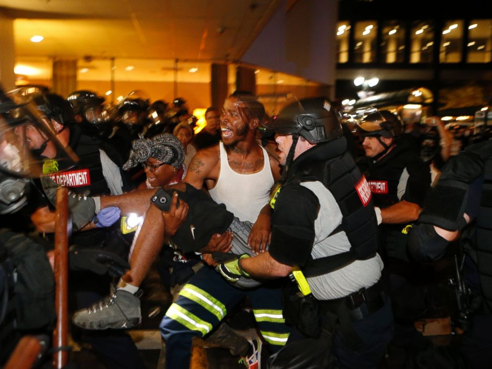 PHOTO: Police and protesters carry a seriously wounded protester into the parking area of the the Omni Hotel during a march to protest the death of Keith Scott Sept. 21, 2016 in Carolina.