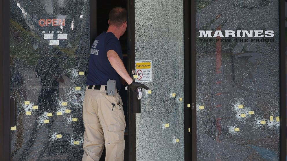 A member of the F.B.I. Evidence Response Team walks through a bullet riddled door as he investigates the shooting at the Armed Forces Career Center/National Guard Recruitment Office, July 17, 2015 in Chattanooga, Tennessee.