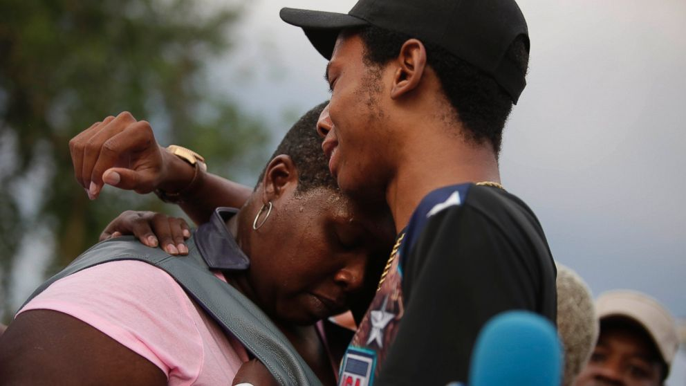 Activist Lamon Reccord, center, consoles Sheila Jones, center, mother of Africa Bass during a vigil for Bass, who was killed as she walked through her apartment complex July 27, 2016, in Chicago.