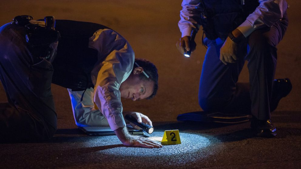Members of the Chicago Police Department look at an evidence marker at the scene of a shooting in the 3100 block of West 83rd Place, Aug. 8, 2016, in the Ashburn neighborhood of Chicago.