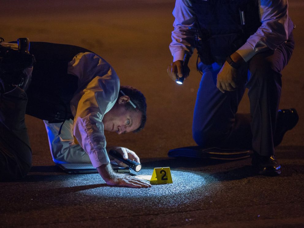 PHOTO: Members of the Chicago Police Department look at an evidence marker at the scene of a shooting in the 3100 block of West 83rd Place, Aug. 8, 2016, in the Ashburn neighborhood of Chicago.