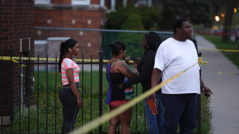 People watch as Chicago Police officers and evidence technicians investigate the scene where a 16-year-old boy was shot in the head and killed and another 18-year-old man was shot and wounded on the 7300 block of South Sangamon Street on April 25, 2016, in Chicago.