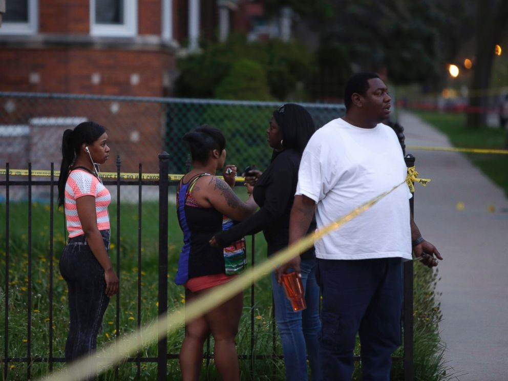 PHOTO: People watch as Chicago Police officers and evidence technicians investigate the scene where a 16-year-old boy was shot in the head and killed and another 18-year-old man was shot and wounded on April 25, 2016, in Chicago.