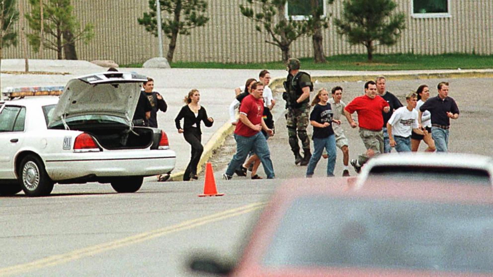 Students from Columbine High School run under cover from police in Littleton, Colo., April 20, 1999.