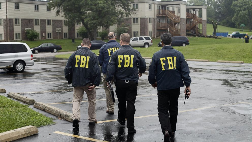 FBI Agents are seen in this Aug. 16, 2014  file photo investigating  the shooting death of 18-year-old Michael Brown at the location where he was killed on Canfield Drive in Ferguson, Mo.