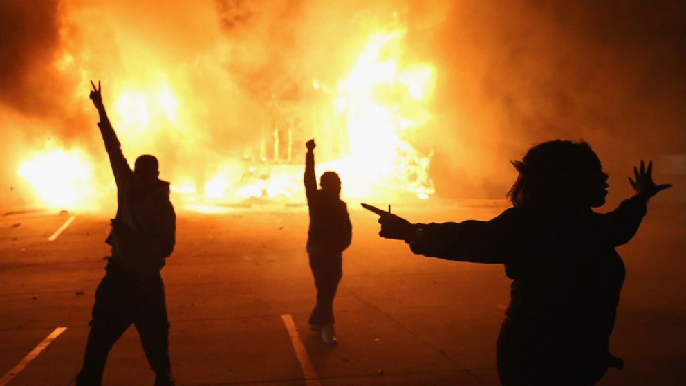 Demonstrators celebrate as a business burns after it was set on fire during riots following the grand jury announcement in the Michael Brown case, Nov. 24, 2014 in Ferguson, Missouri.