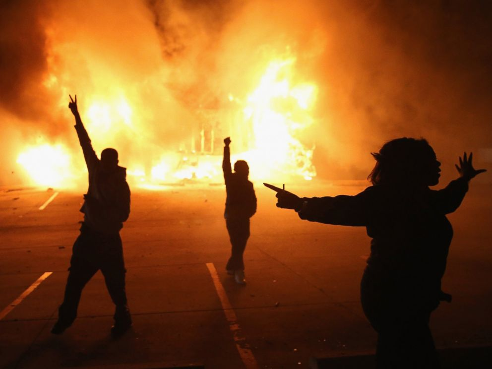 PHOTO: Demonstrators celebrate as a business burns after it was set on fire during riots following the grand jury announcement in the Michael Brown case, Nov. 24, 2014 in Ferguson, Missouri.