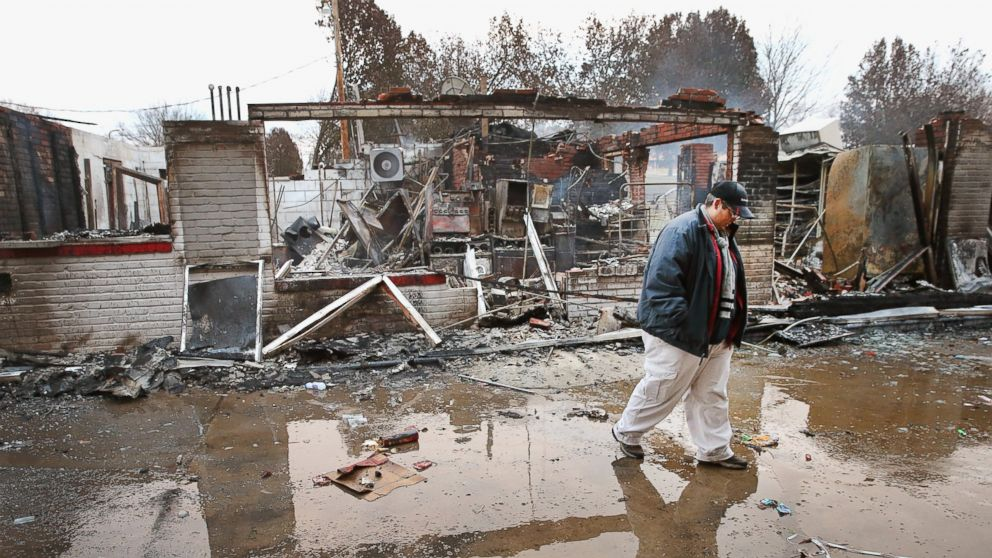 Property manager Terri Willits looks over a gas station she manages that was set on fire when rioting erupted following the grand jury announcement in the Michael Brown case, Nov. 25, 2014 in Dellword, Mo.
