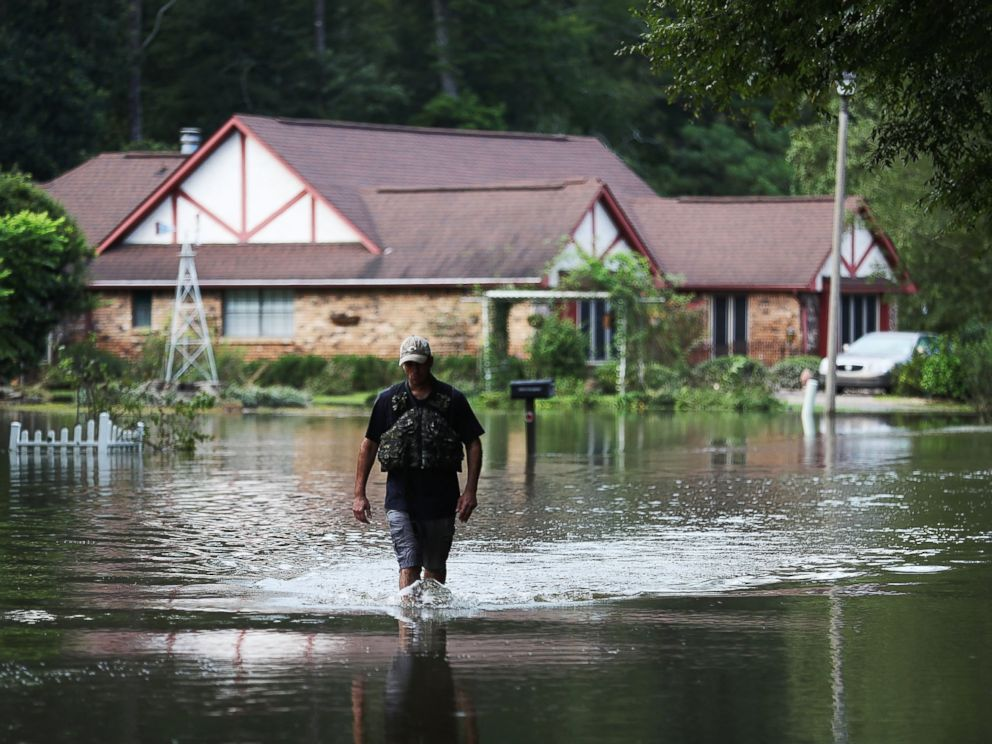 PHOTO: Ryan Evans walks along a flooded road, Aug. 15, 2016, in Baton Rouge, Louisiana.