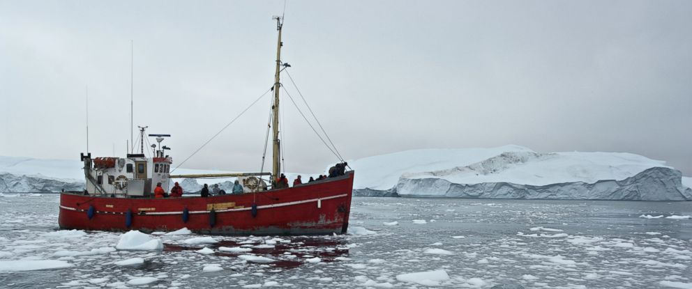 PHOTO:A ship is seen among the icebergs that have broken off the Sermeq Kujalleq Glacier in Ilulissat, Greenland.