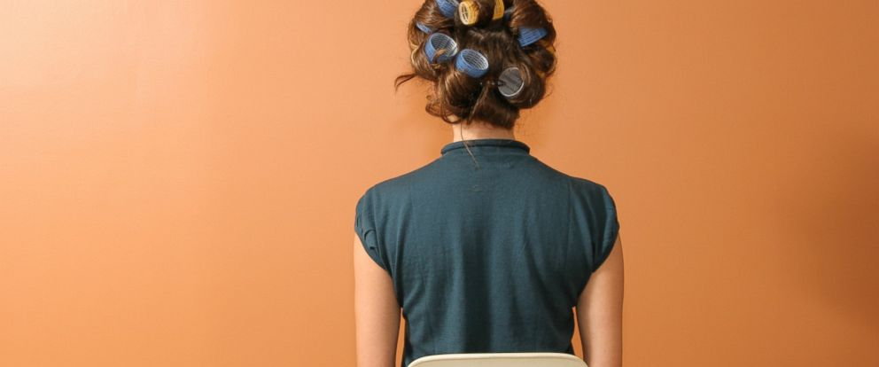 PHOTO: A woman sits wearing curlers in her hair.
