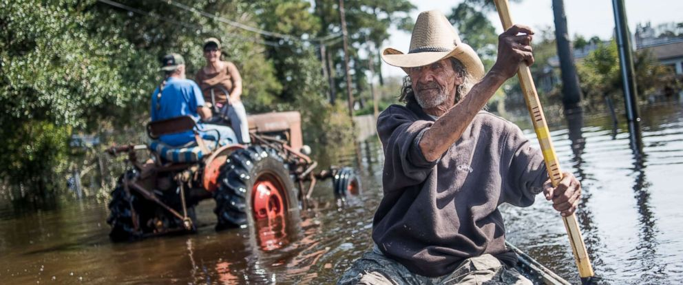 PHOTO: Harvey Wearnes paddles a canoe through a flooded street in his neighborhood, Oct. 15, 2016, in Lumberton, North Carolina.