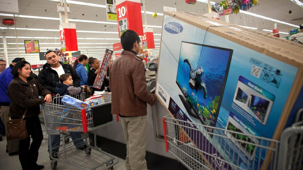 Shoppers wait in a check out line at a Kmart store during the Black Friday sales, Nov. 23, 2012, in Braintree, Mass.