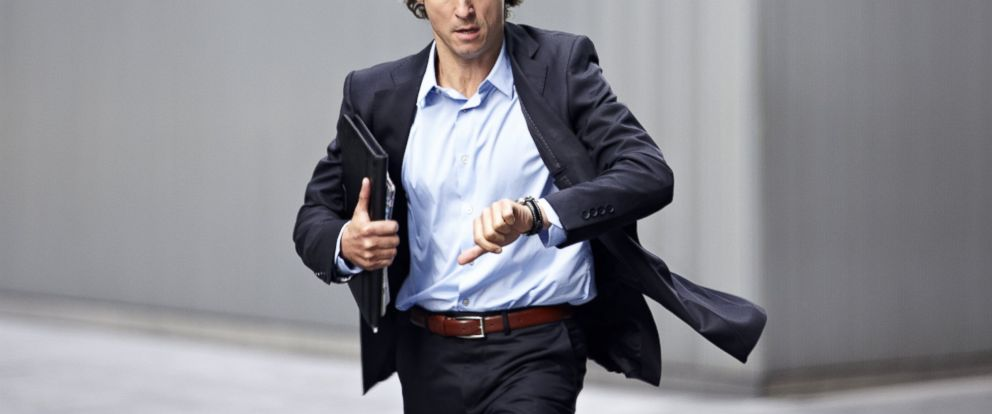 PHOTO: A businessman is pictured checking his wristwatch while rushing in this stock image.
