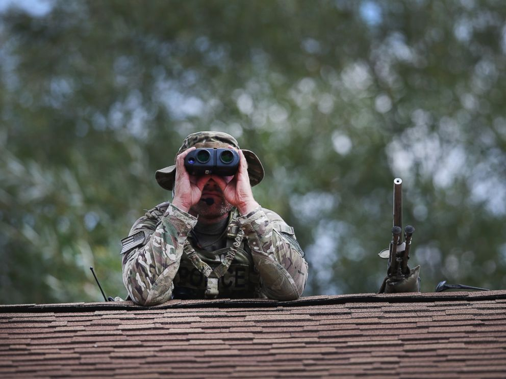 PHOTO:A police sniper keeps watch from the roof of a home while other police search nearby for suspects involved in the shooting of an officer, Sept. 1, 2015, in Fox Lake, Ill.