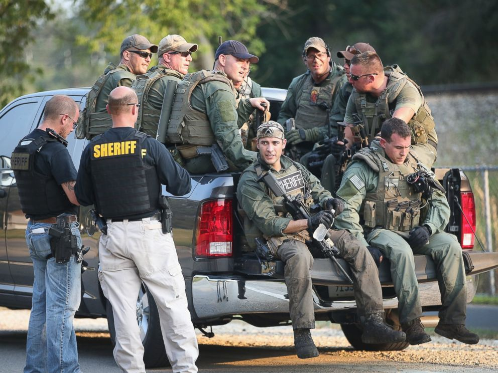 PHOTO: Police officers get a break after coming off a search mission as temperatures exceeded 90 degrees during a manhunt for three suspects in the murder of a Fox Lake Police officer, Sept. 1, 2015, in Fox Lake, Ill.
