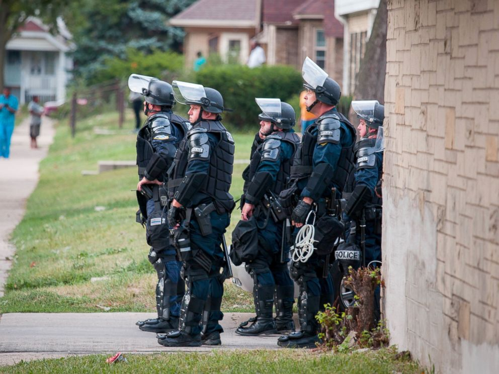 PHOTO: Police in riot gear wait in an alley after a second night of clashes between protestors and police, Aug. 15, 2016, in Milwaukee, Wisconsin.