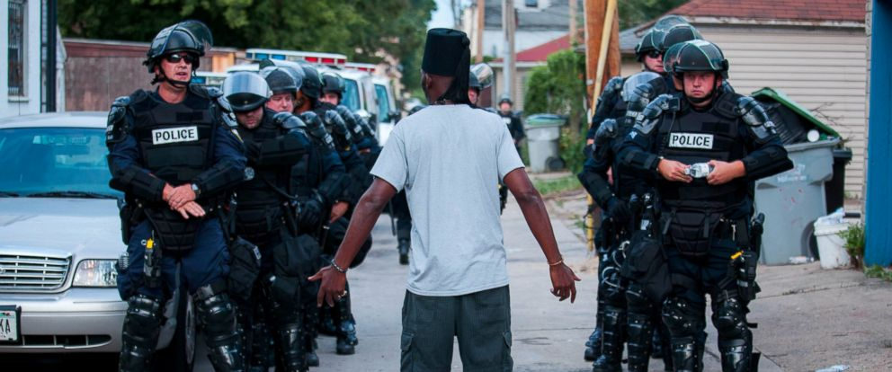 PHOTO: A man talks to police in riot gear as they wait in an alley after a second night of clashes between protestors and police, Aug. 15, 2016, in Milwaukee, Wisconsin.