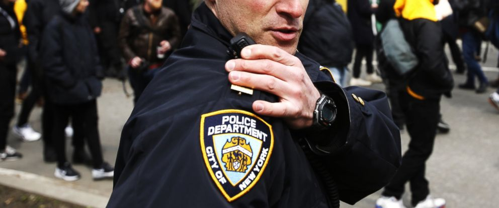 PHOTO: An NYPD officer talks on his radio while people take part in a protest against Republican presidential candidate Donald Trump, March 19, 2016, in New York.