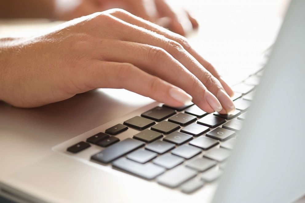 A woman is pictured typing on a laptop in this stock image.