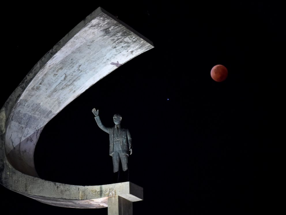 PHOTO: The moon during a total lunar eclipse over the Juscelino Kubitschek Memorial in Brasilia, Brazil.