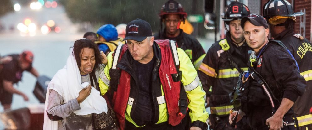 PHOTO:Charlene Stennis is escorted to safety after her son was rescued from a stranded vehicle in a flooded roadway, Oct. 4, 2015, in Columbia, S.C.