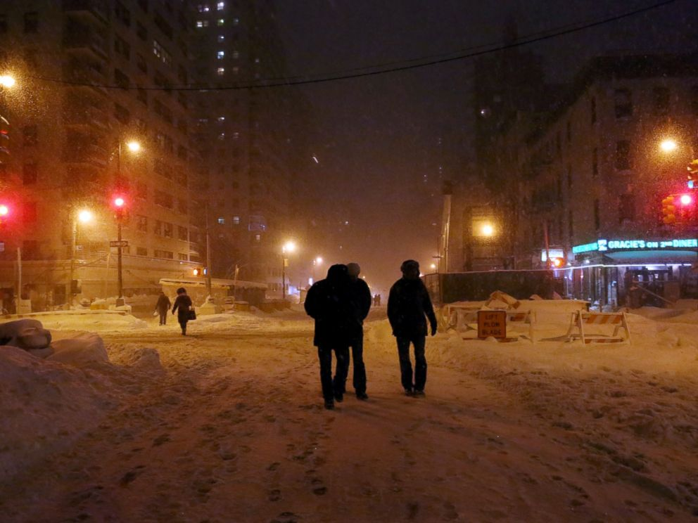 PHOTO: NEW YORK, NY - JANUARY 23: Pedestrians walk through the snowy streets of the Upper East Side, as all cars but emergency vehicles are banned from driving on the road on January 23, 2016 in New York City.
