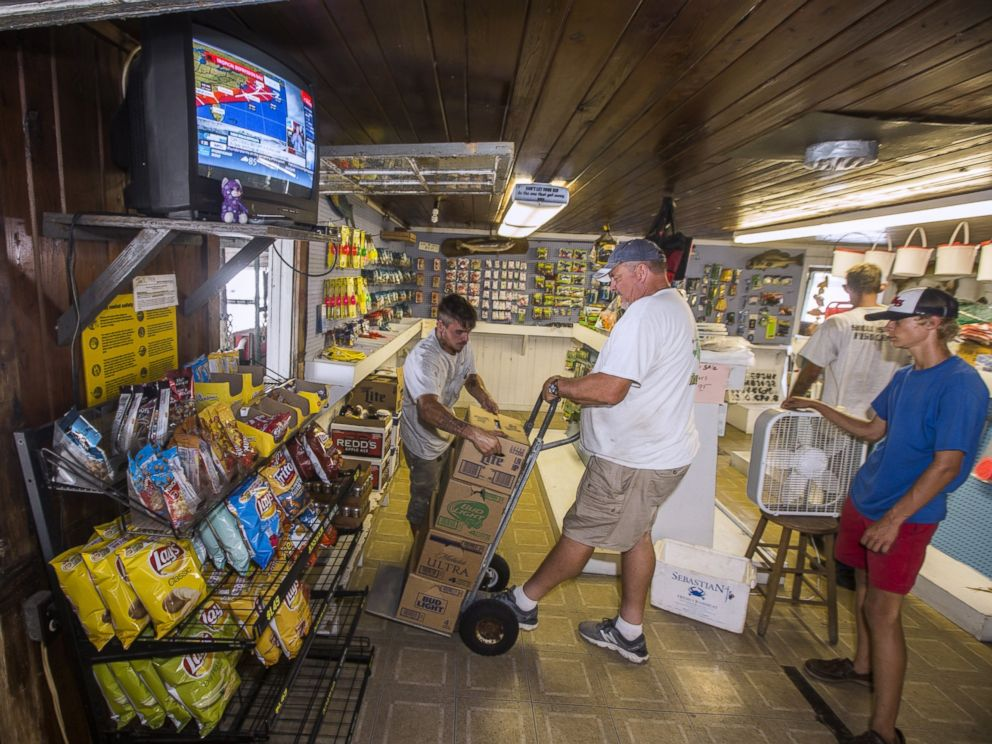 PHOTO: Hurricane warnings play on the television while Tim Rozelle, left, stacks beer on a cart held by Murray Stokes, Aug. 31, 2016 in Saint Marks, Florida.