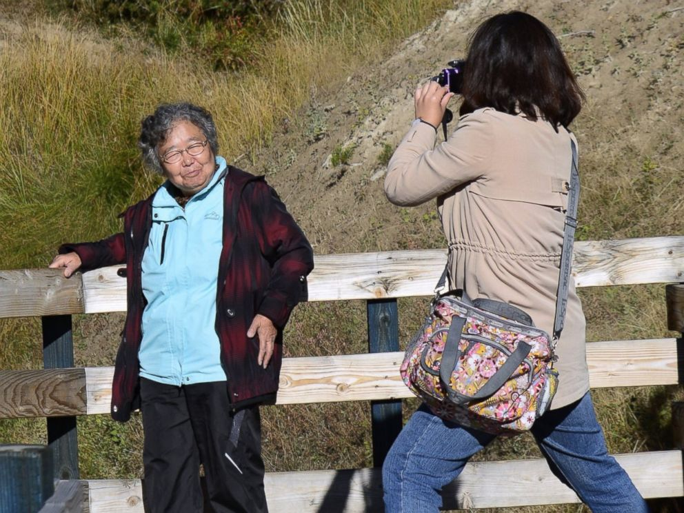 PHOTO: Tourists from China take souvenir photographs on a boardwalk leading to Dragons Mount Spring, a popular geothermal attraction in Yellowstone National Park in Wyoming on Sept. 25, 2014.