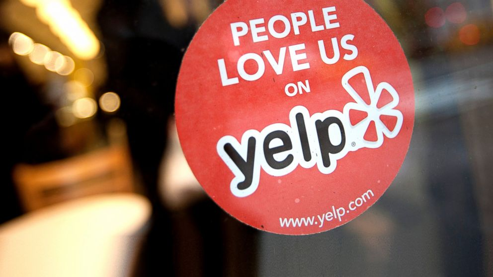 The Yelp Inc. logo is displayed in the window of a restaurant in New York, March 1, 2012.