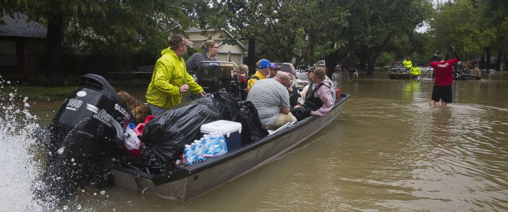 PHOTO: A large rescue boat is pulled through shallow water after flooding caused by heavy rain during Hurricane Harvey August 29, 2017 in the Bear Creek neighborhood in west Houston, Texas.