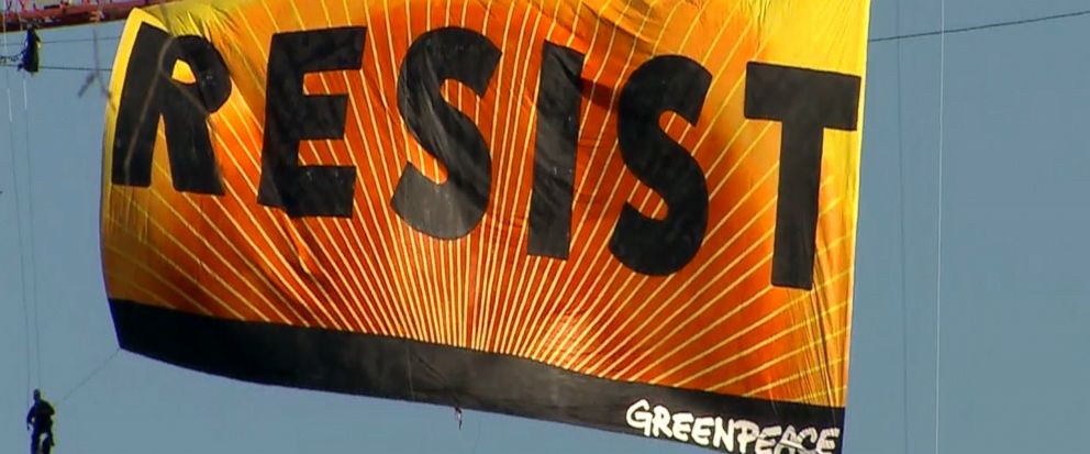 "Greenpeace protesters scaled a crane in Washington, D.C. to unfurl a giant banner that reads ""RESIST"" in protest against President Donald Trump."