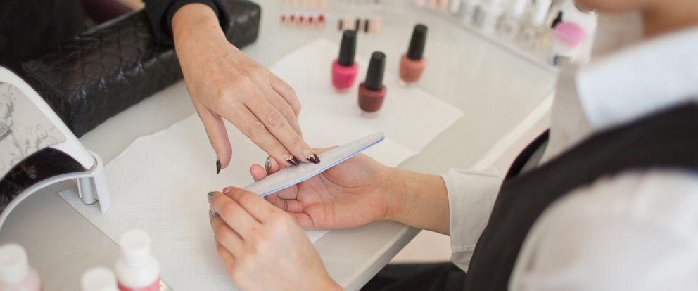 PHOTO: Manicurist polishing finger nails at beauty salon.