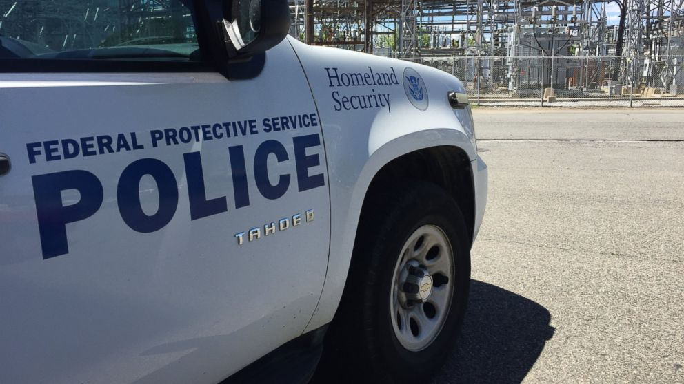 A Department of Homeland Security vehicle is parked near an electric company's equipment.