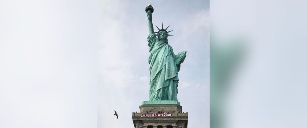 """PHOTO: A banner reading """"Refugees Welcome"""" was illegally placed at the base of the Statue of Liberty Tuesday, Feb. 21, 2017."""
