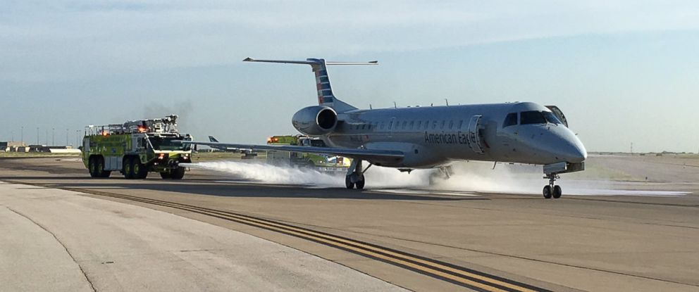 PHOTO: Emergency responders spray water on the brakes of an American Eagle flight at Dallas/Ft. Worth International Airport on June 27, 2016.