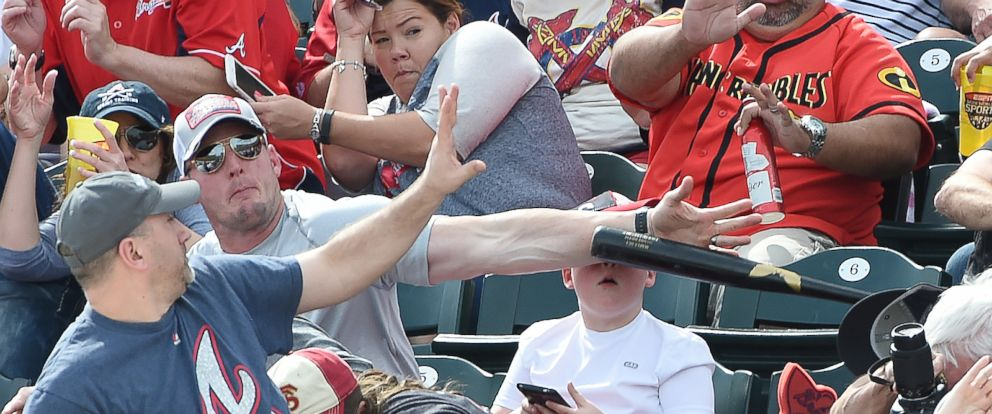 PHOTO: A fan knocks down a bat thrown into the stands by the Pirates Danny Ortiz during a spring training game against the Braves on March 5, 2016, at Champion Stadium in Lake Buena Vista, Fla.