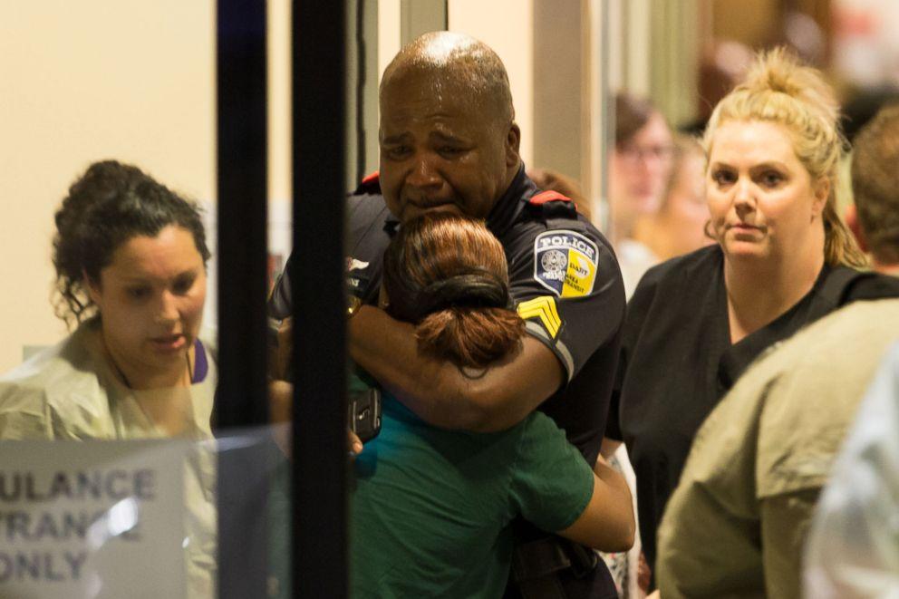 PHOTO: A DART police officer receives comfort at Baylor University Hospital emergency room entrance, July 7, 2016, in Dallas.