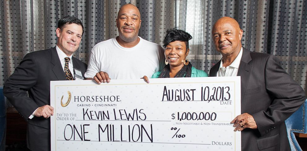 PHOTO: Kevin Lewis and fiancée Lodi (center), hold a check for Lewis' $1 million prize with Horseshoe Cincinnati General Manager Kevin Kline (far left), and local radio personality Lincoln Ware (far right)