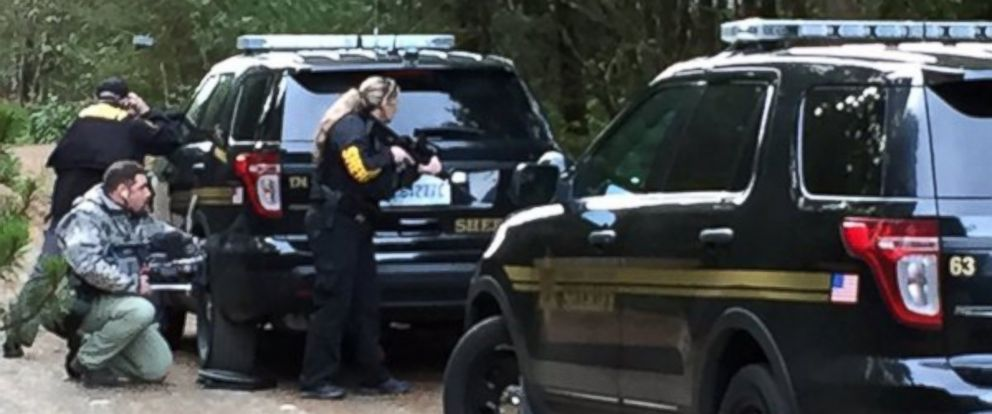 PHOTO: Mason County police officers stand with their guns drawn in a shooting scene in Belfair, Washington where a gunman killed four people and himself.