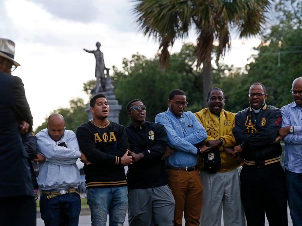 PHOTO: Graduate members of Alpha Phi Alpha Fraternity pray during a social action prayer vigil across the street from the Jefferson Davis monument in New Orleans, Thursday, May 4, 2017.