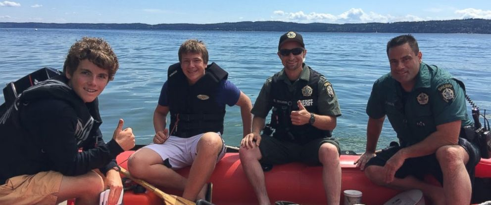 PHOTO: Two teens and Camano Island Sheriff's Department officers with recovered boat in Washington on July 21, 2016.
