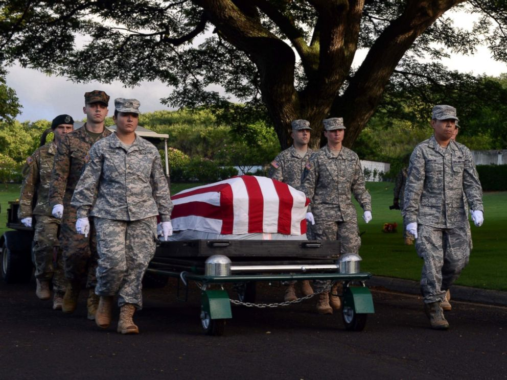 PHOTO: Members of the Defense POW/MIA Accounting Agency march alongside a disinterred casket holding the remains of unknown USS Oklahoma service members during a ceremony at the National Memorial Cemetery of the Pacific in Honolulu, Nov. 5, 2015.