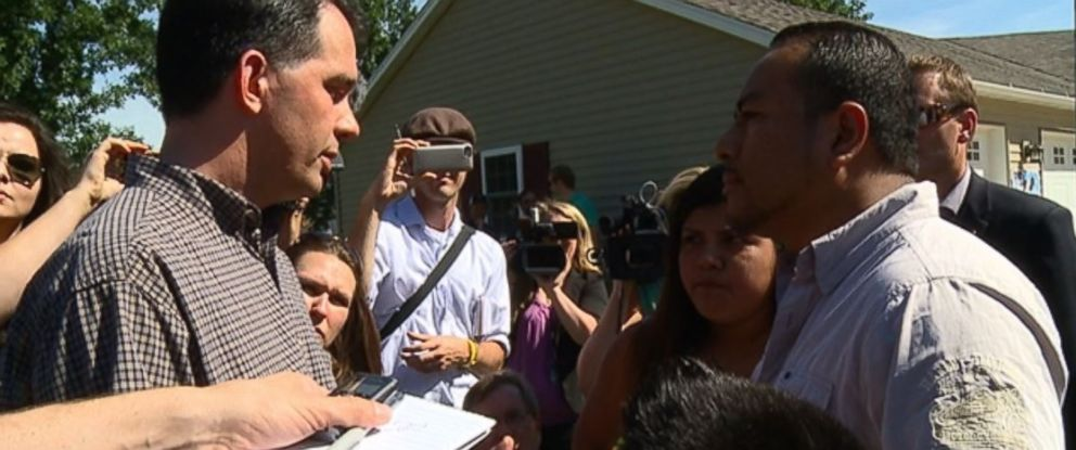 PHOTO: Scott Walker talks to Jose Flores and his children during a campaign stop in Plainfield, Iowa, July 19, 2015.