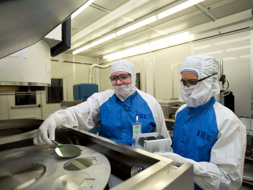 PHOTO: Lawrence Livermore engineers Angela Tooker and Vanessa Tolosa load silicon wafers into a metal deposition chamber during the development of neural devices.