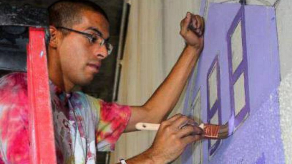 """Muralist Antonio """"Tony"""" Ramos, seen painting, was shot and killed last year. His family is filing a claim against ICE over a stolen gun."""